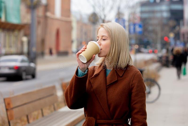 Mooie blonde vrouw met kop koffie op de straat van de stad stock fotografie
