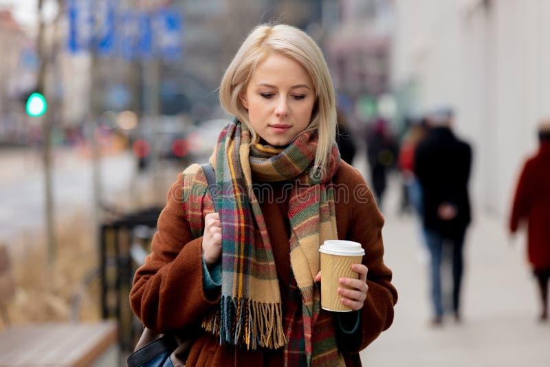 Mooie blonde vrouw met kop koffie op de straat van de stad stock afbeeldingen