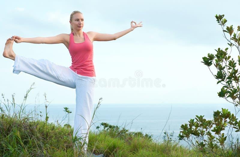 Mooie blonde vrouwelijke training op het strand royalty-vrije stock afbeelding