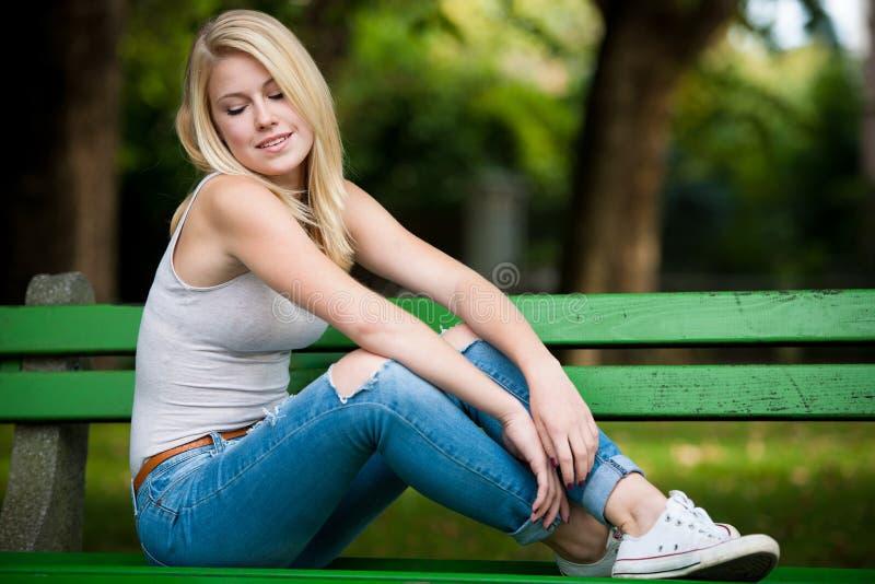 Mooie blonde woamn rust op een bank in park royalty-vrije stock afbeeldingen