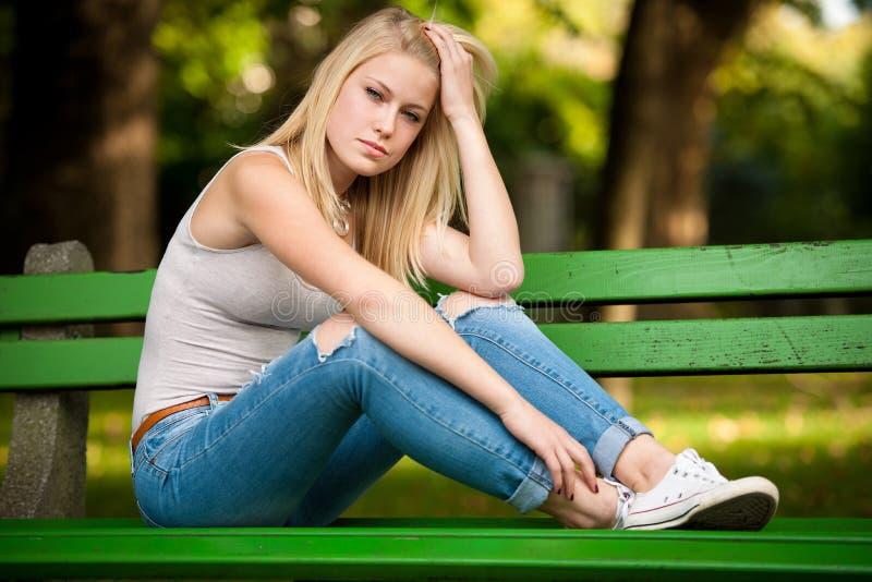 Mooie blonde woamn rust op een bank in park stock foto