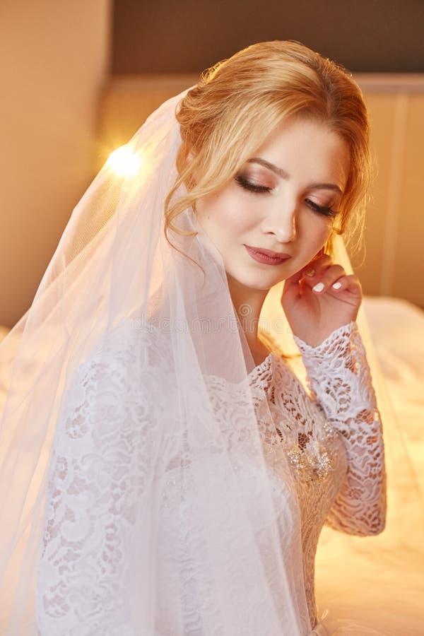 Mooie blondebruid in de ochtend in een witte huwelijkskleding w royalty-vrije stock afbeelding