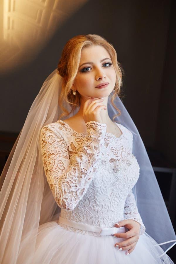 Mooie blondebruid in de ochtend in een witte huwelijkskleding w royalty-vrije stock foto's