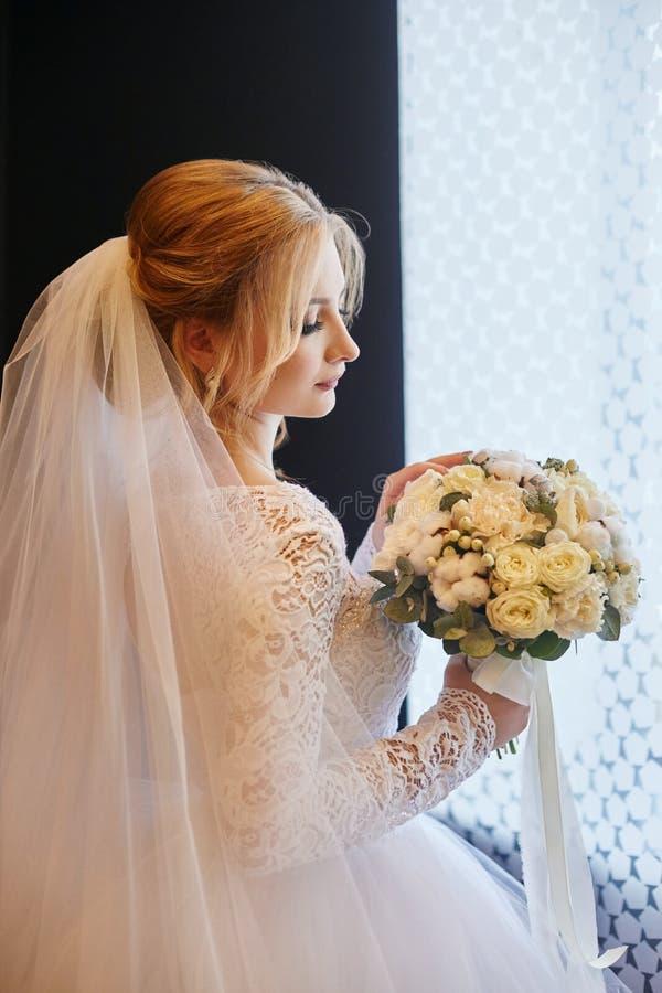 Mooie blondebruid in de ochtend in een witte huwelijkskleding w stock afbeeldingen