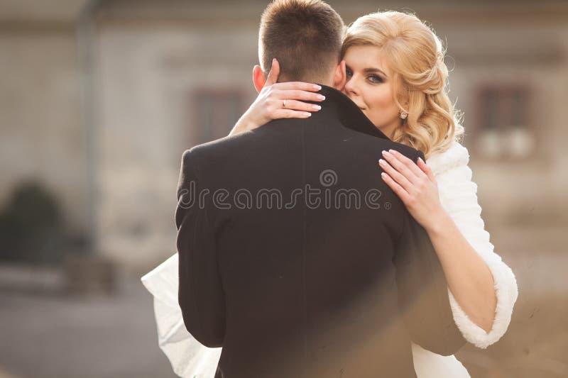 Mooie blondebruid die knappe bruidegom in zwarte laag in t kussen royalty-vrije stock fotografie