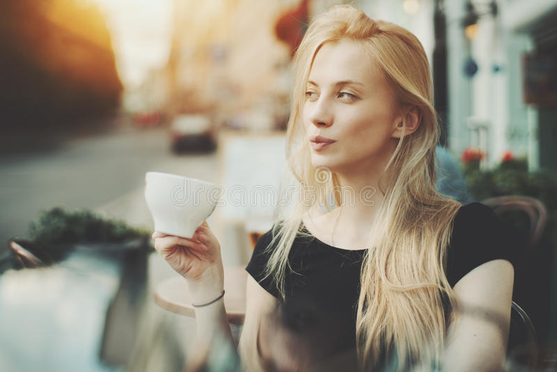 Mooie blondedame alleen in straatkoffie stock foto's