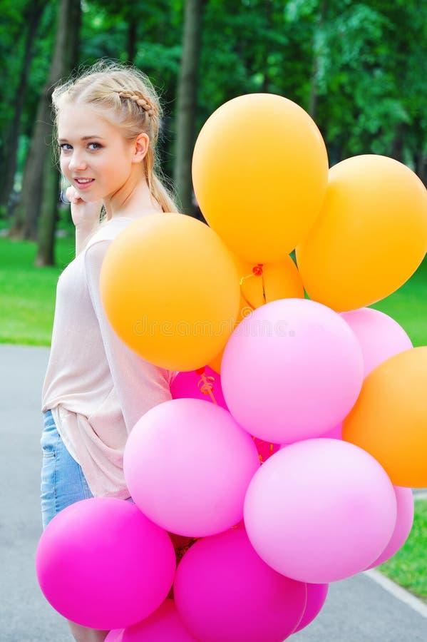 Mooie blondetiener met ballons stock afbeelding