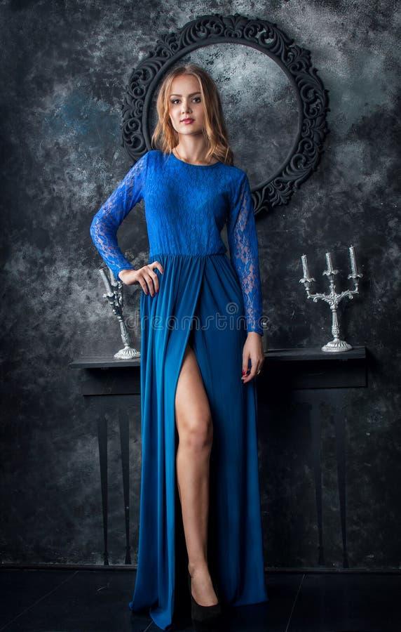 Mooie blondevrouw in blauwe kleding in donker binnenland stock afbeelding