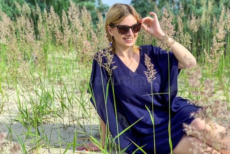 Mooie blondevrouw in blauwe kleding en zonnebril die terwijl het zitten op grond onder gras bij de zomerweide, die haar houden st stock afbeelding