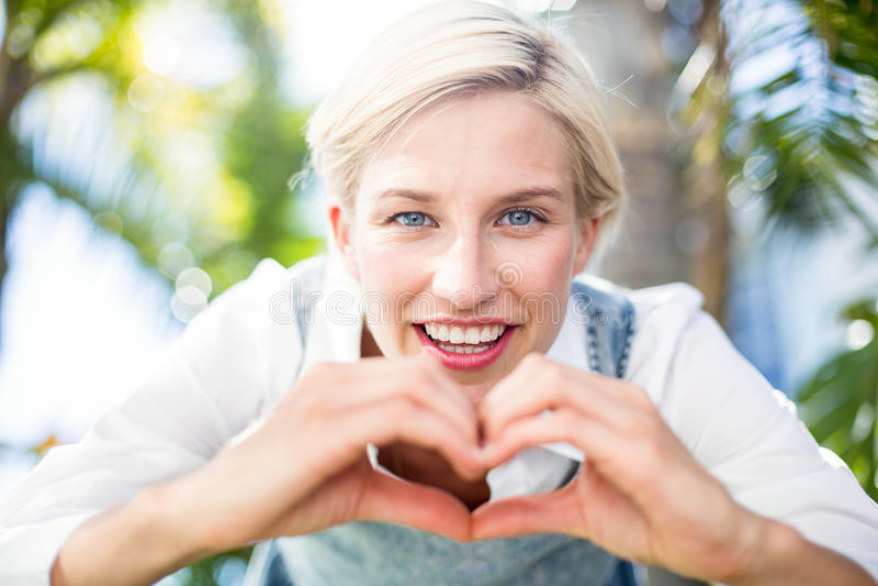 Mooie blondevrouw die bij de camera glimlachen en hartvorm met haar handen doen stock fotografie