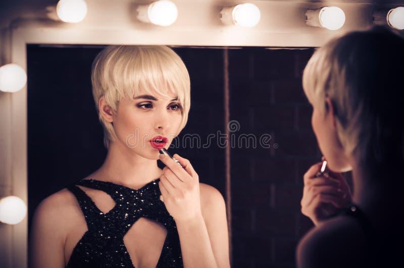 Mooie Blondevrouw die een Spiegel onderzoeken bij zich stock fotografie