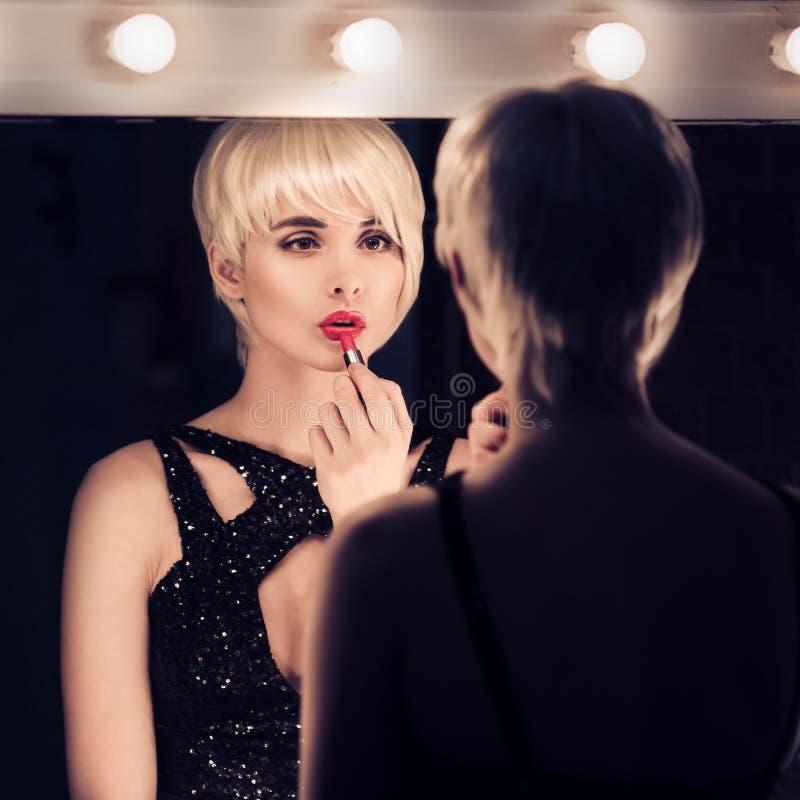 Mooie Blondevrouw die een Spiegel onderzoeken bij zich royalty-vrije stock fotografie