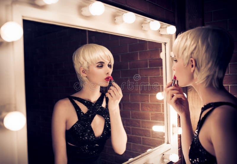 Mooie Blondevrouw die een Spiegel onderzoeken in zich en Appl stock foto's
