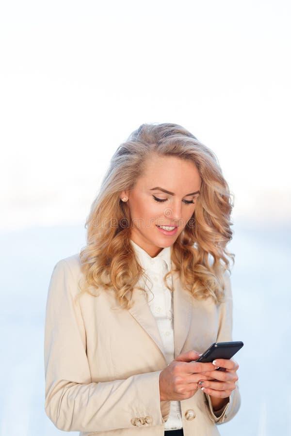 Mooie blondevrouw die mobiele telefoon en het glimlachen gebruiken stock afbeeldingen