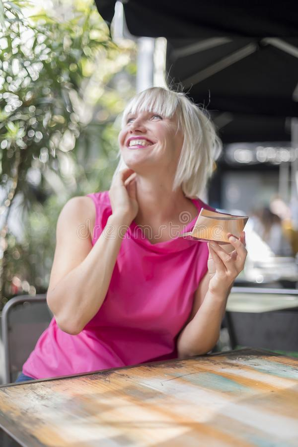 Mooie blondevrouw die omhoog het gebruiken van een zilveren spiegel maken - Outdoo stock afbeelding
