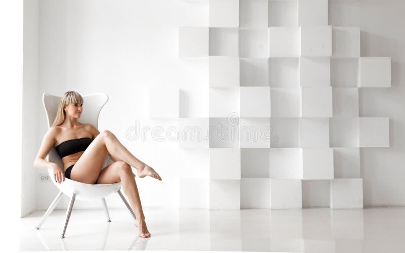 Mooie blondevrouw, die op een stoel zitten royalty-vrije stock foto's
