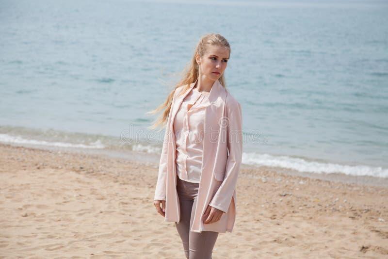 Mooie blondevrouw die op het zandige overzees-strand lopen royalty-vrije stock fotografie