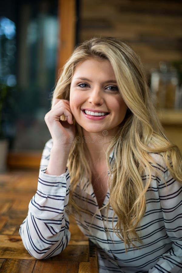 Mooie blondevrouw die op lijst in café leunen stock afbeelding