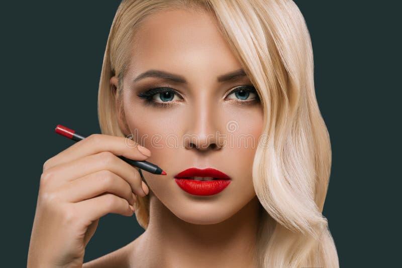 mooie blondevrouw die rode lippen met kosmetisch potlood maken, stock afbeelding