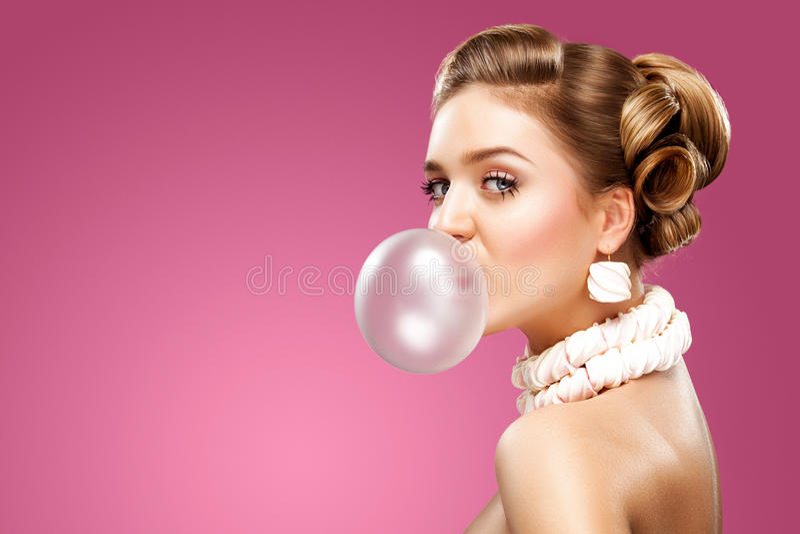 Mooie blondevrouw die roze kauwgom blazen Het Portret van de manier stock foto
