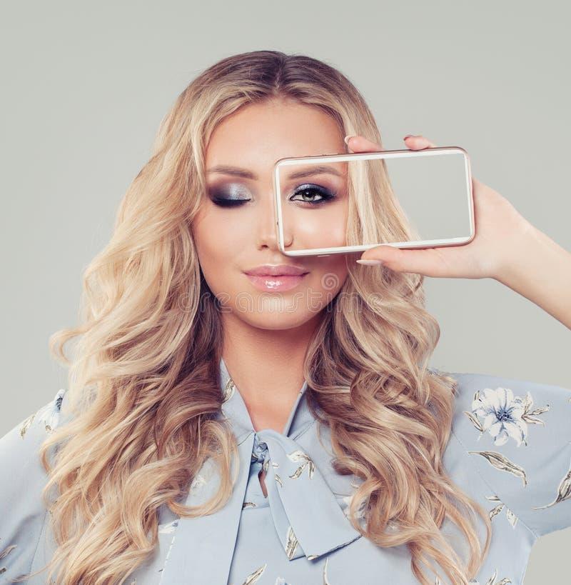Mooie blondevrouw die smartphone gebruiken stock foto