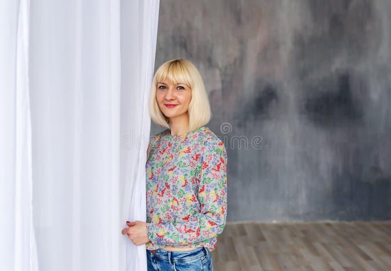 Mooie blondevrouw die zich in studio dichtbij wit gordijn bevinden royalty-vrije stock afbeelding