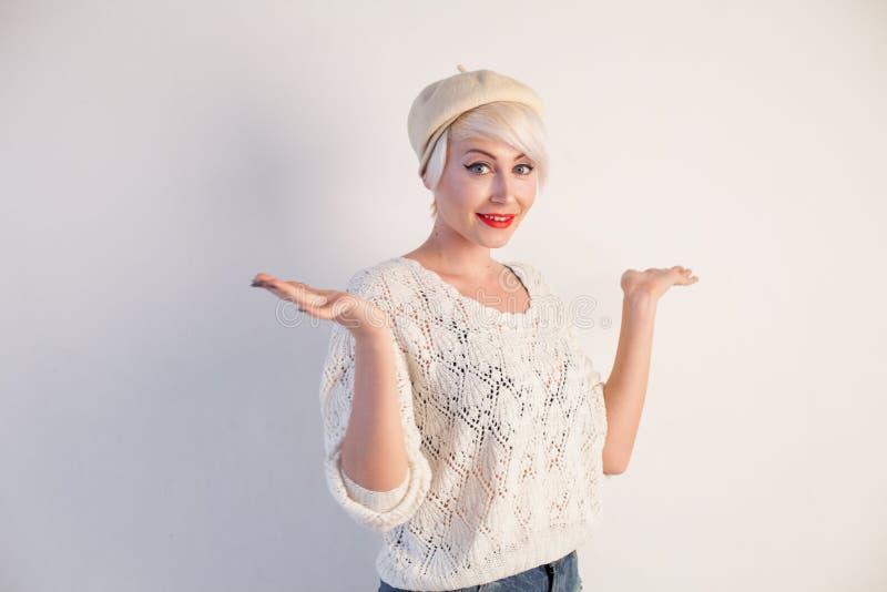 Mooie blondevrouw in een baret en een heldere kleding op een witte achtergrond stock foto's
