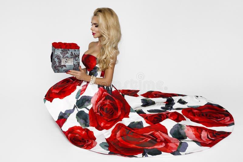 Mooie blondevrouw in een elegante avondtoga met rode rozen, holding de gift van Valentine, een flowerbox met bloemen schoonheid royalty-vrije stock afbeeldingen