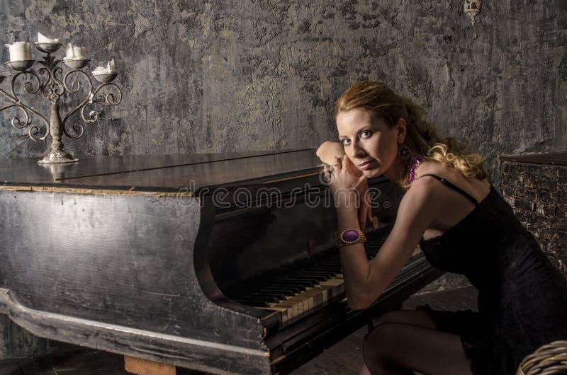 Mooie blondevrouw in een elegante kleding bij de piano in een donkere ruimte stock fotografie