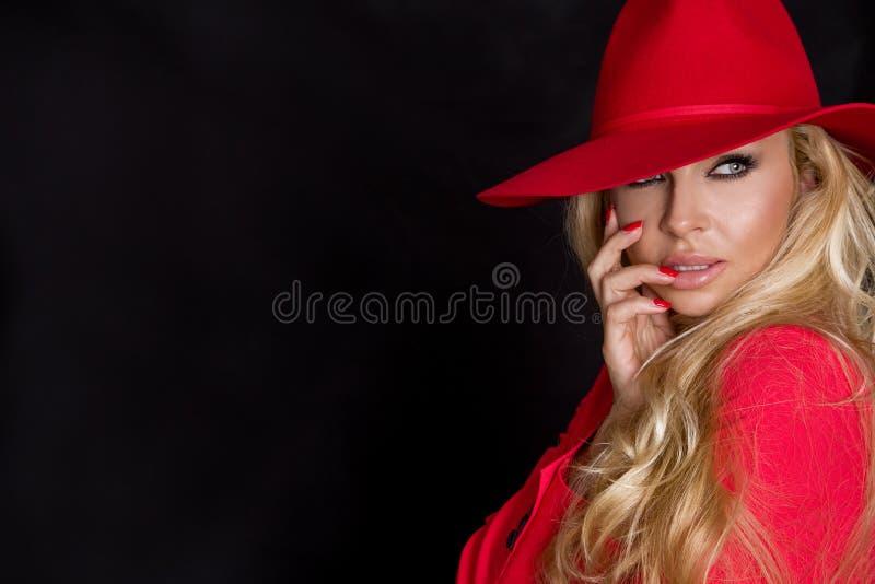 Mooie blondevrouw in een rode hoed, een rood jasjekostuum en rode verleidende lippen stock foto