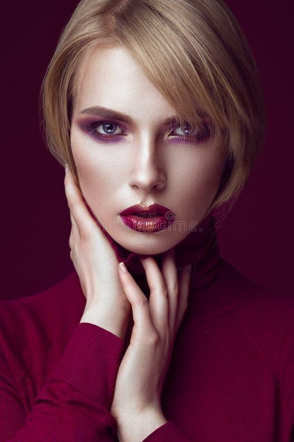 Mooie blondevrouw in een rode sweater met heldere make-up en donkere lippen Het Gezicht van de schoonheid stock afbeelding