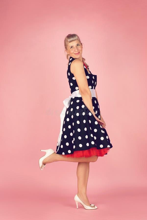 Mooie blondevrouw in een stipkleding, tribunes zijdelings en opgeheven haar been, speld-op stijl op een roze achtergrond stock afbeelding