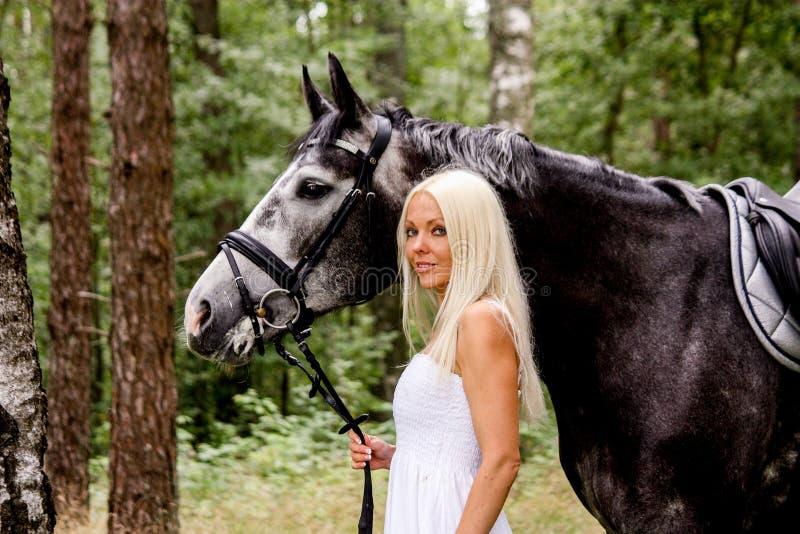 Mooie blondevrouw en grijs paard in bos royalty-vrije stock foto