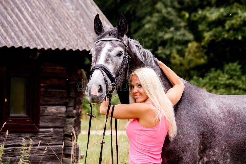 Mooie blondevrouw en haar paard op plattelandsgebied royalty-vrije stock foto