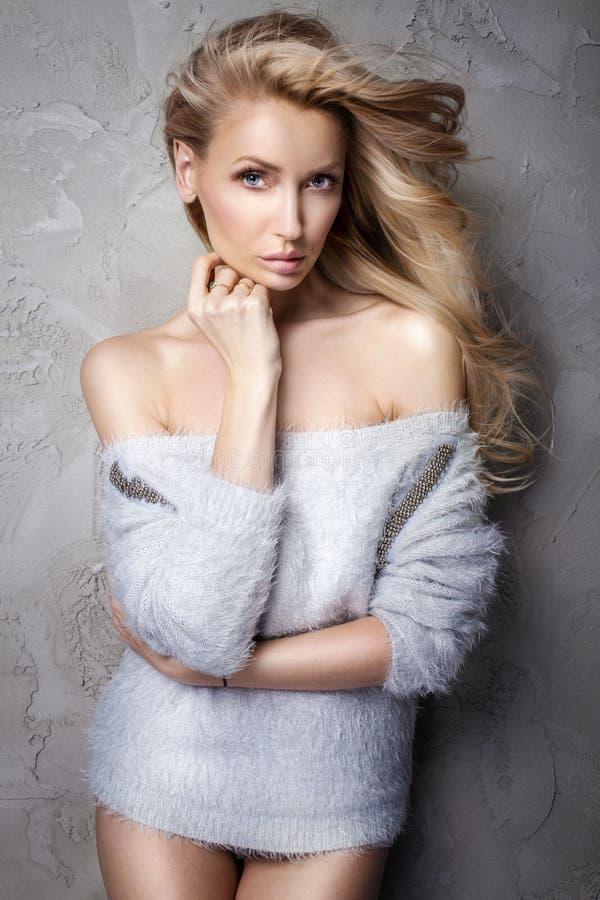 Mooie blondevrouw in grijze sweater stock afbeeldingen