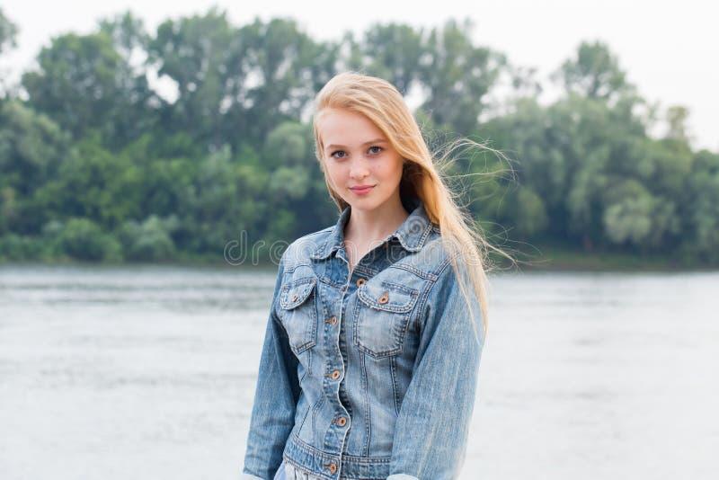 Mooie blondevrouw in jeans en met lang haar op aardachtergrond met exemplaarruimte royalty-vrije stock fotografie