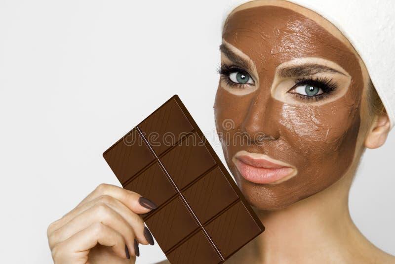 Mooie blondevrouw met een gezichtsmasker, beauty spa Het masker van het chocoladegezicht royalty-vrije stock fotografie