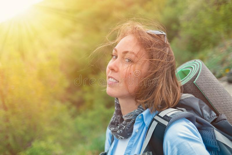 Mooie blondevrouw met een rugzak achter het stellen op een bergachtergrond met groene bos Dichte omhooggaand Concept toerisme stock foto