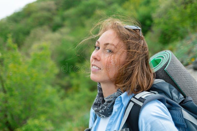 Mooie blondevrouw met een rugzak achter het stellen op een bergachtergrond met groene bos Dichte omhooggaand Concept toerisme royalty-vrije stock afbeelding