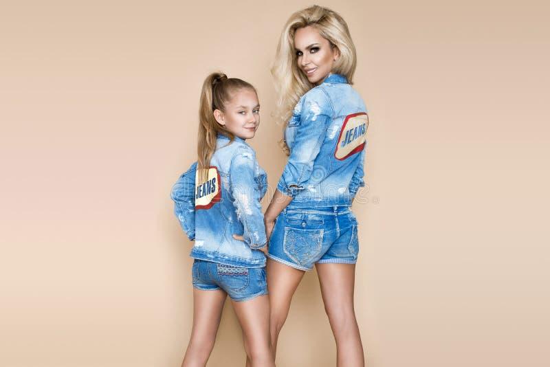 Mooie blondevrouw met haar dochter in een denimjasje en borrels Mannequins in jeans kleding royalty-vrije stock foto