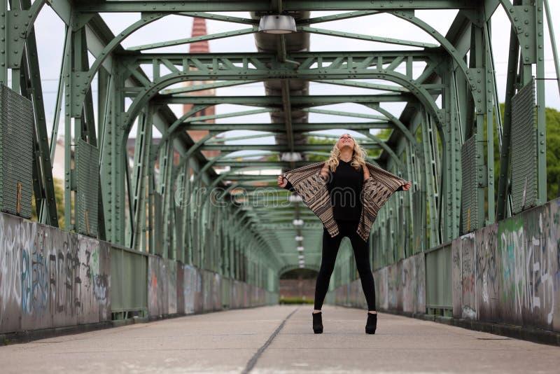 Mooie blondevrouw op een brug met graffiti stock afbeelding