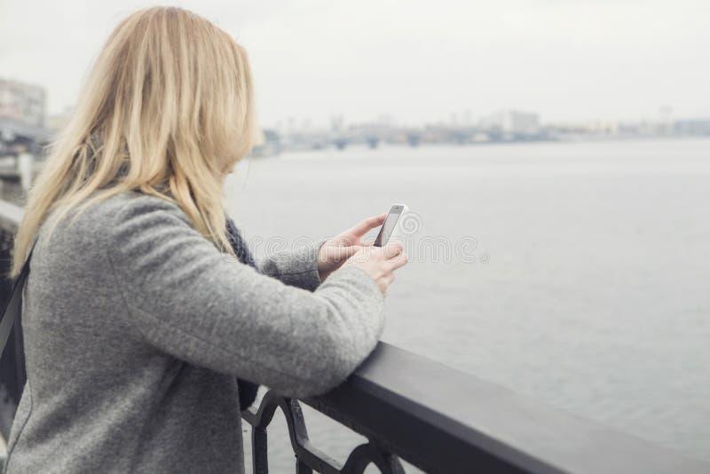 Mooie blondevrouw op een gang in Europese stad die smar haar gebruiken royalty-vrije stock foto