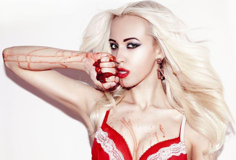 Mooie blondevrouw in rood ondergoed, een handvol van aardbei royalty-vrije stock afbeelding