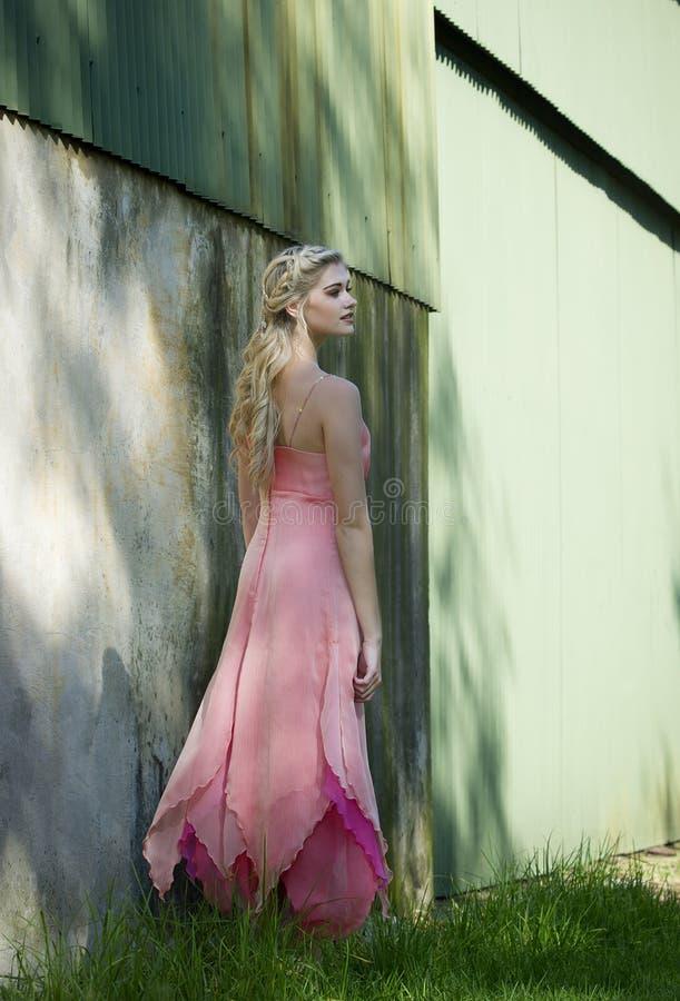 Mooie blondevrouw in roze buiten een rustiek gebouw royalty-vrije stock afbeeldingen