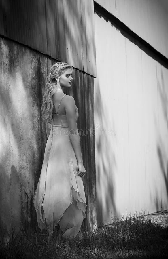 Mooie blondevrouw in vrouwelijke kleding buiten een rustiek gebouw stock foto