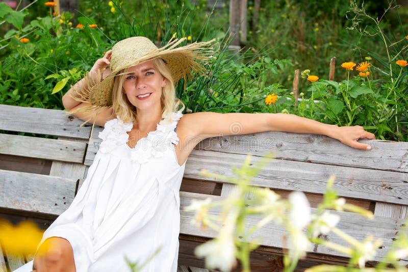 Mooie blondevrouw in witte kledingszitting buiten in tuin en glimlachen royalty-vrije stock afbeelding