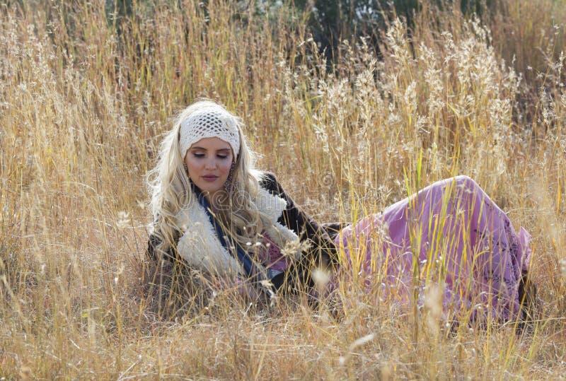 Mooie Boheemse blondevrouw die in gebied van gras liggen royalty-vrije stock foto