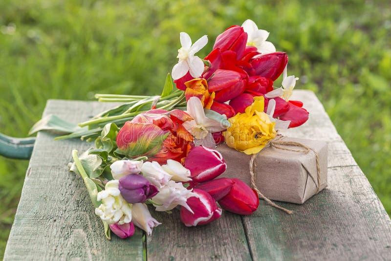 Mooie bos van multicolored tulpen en hand - gemaakte giftdoos op de oude bank royalty-vrije stock afbeelding