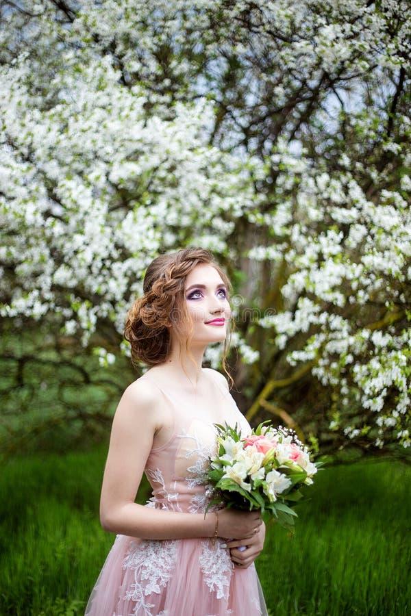 Mooie bruid in de holdingsboeket van de huwelijkskleding in handen stock foto