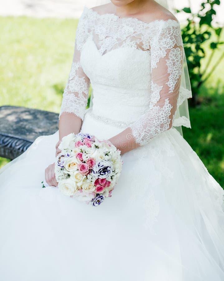 Mooie bruid in de witte kleding van het kanthuwelijk met huwelijksboeket royalty-vrije stock afbeeldingen